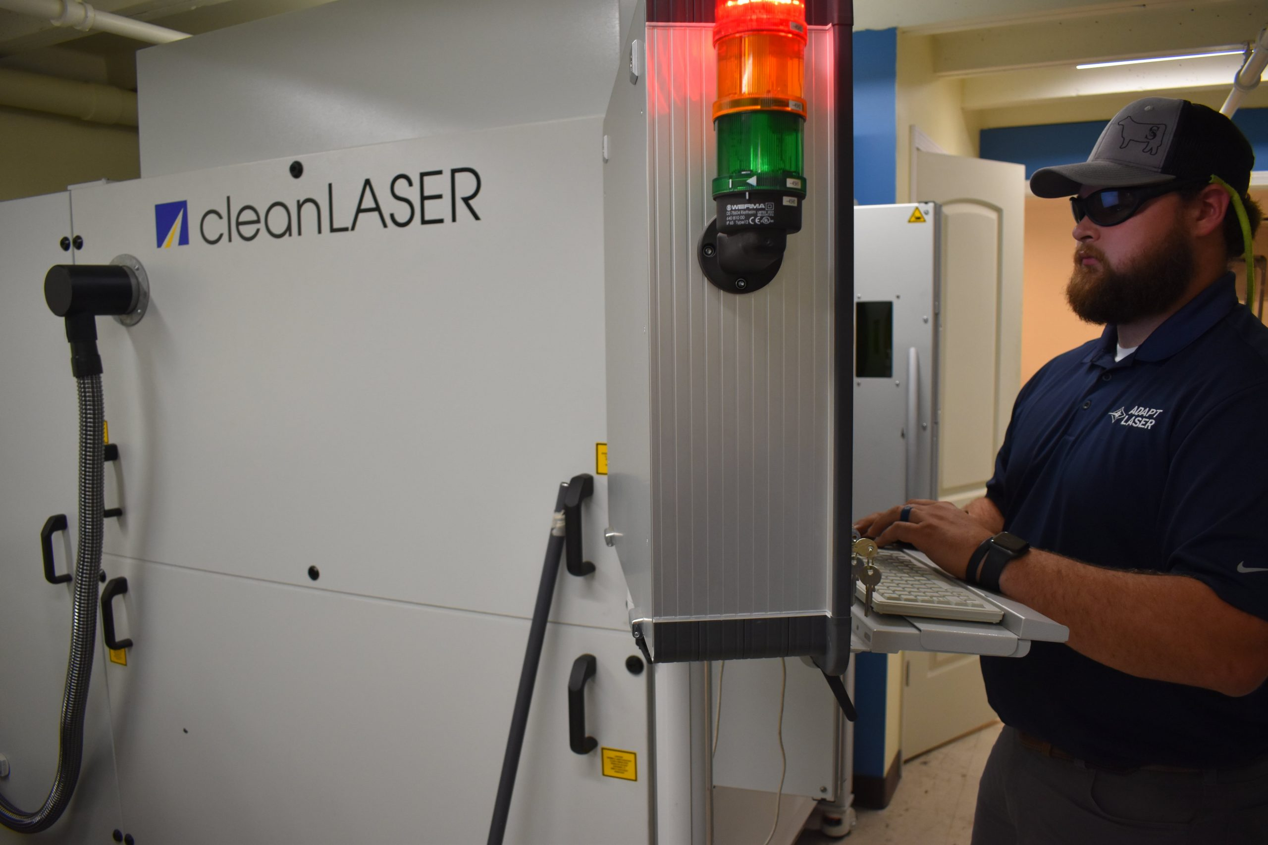 service tech stands at keypad in front of large Cleancell laser